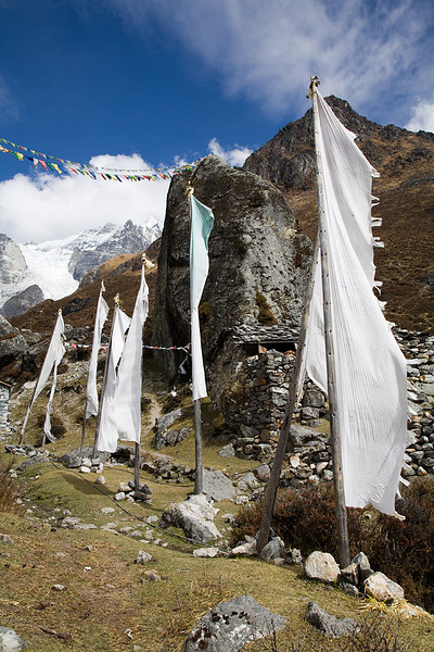 Prayer flags snapping in the wind at the Buddhist monastery of Kyanjin Gompa. / Langtang Himal, Nepal
