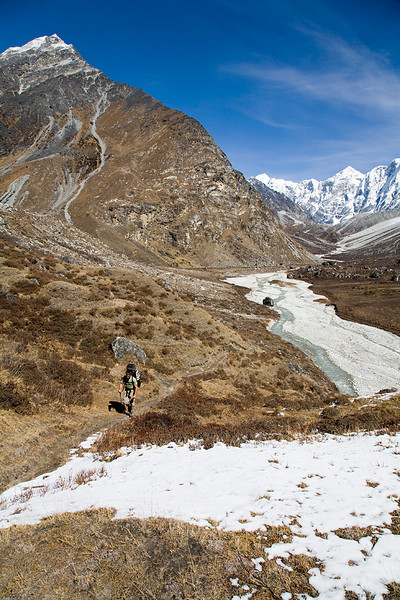 A hiker ascends from the summer grazing area of Langshisa Kharka. / Langtang Himal, Nepal
