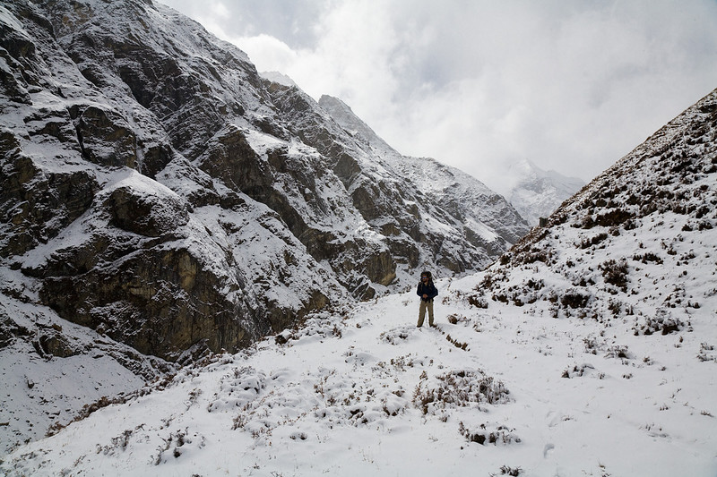 A hiker contemplates the grandeur of the Upper Langtang Valley, a world of granite, ice and cloud. / Langtang Himal, Nepal