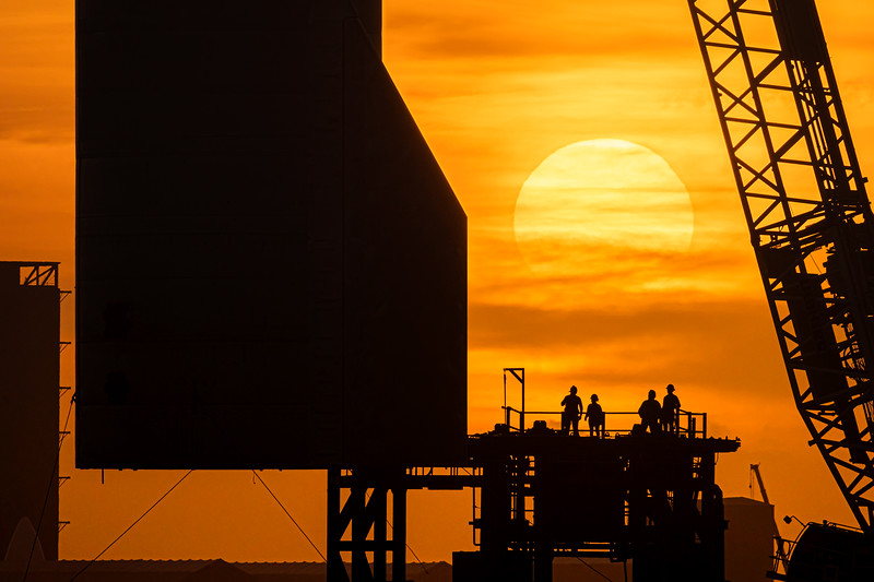 The sun sets behind Starship SN10 as it is lifted onto the Pad A launch mount.