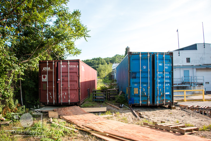 Pre Mural Canal front of red and blue shipping containers