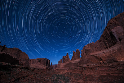 A full moon illuminates Park Avenue in Arches National Park