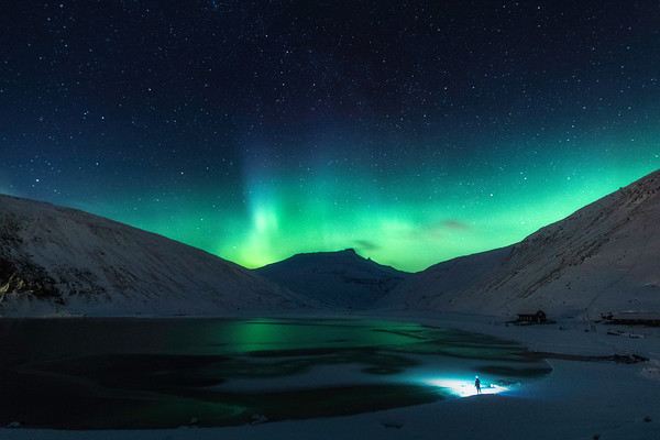 Man watching the Northern Lights  on a cold winter day at Leynavatn - Faroe islands.