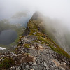 View from the clouded summit ridge of Mt. Reinebringen, Lofoten.