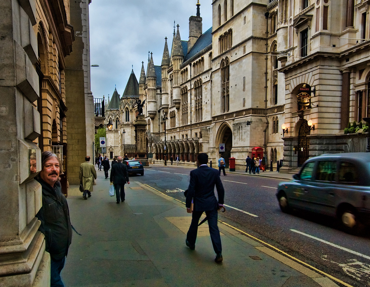 Minister of Funny Walks on Fleet Street. Dig the cool parapets.