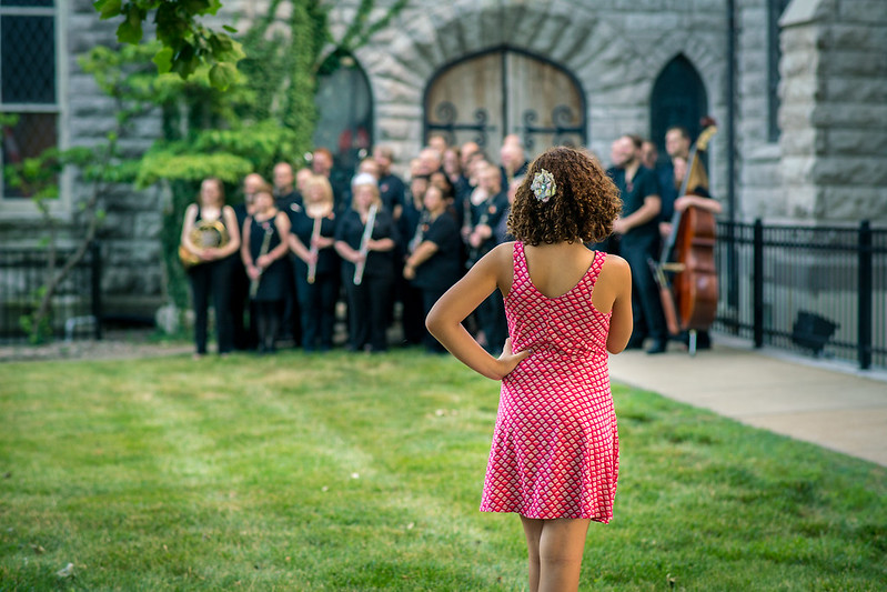A young lady twirls and dances while watching MidAmerica Freedom Band pose for a photograph.