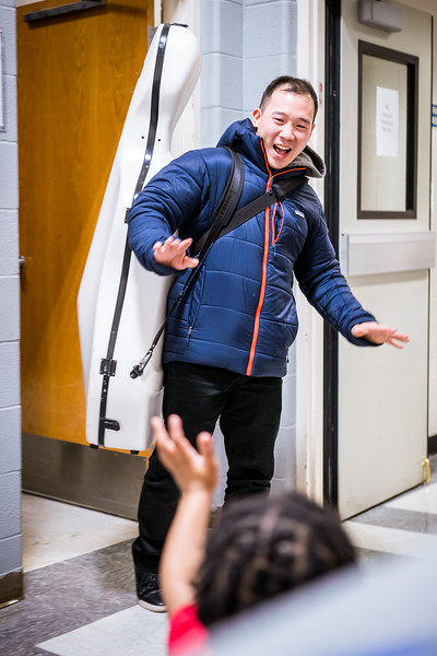 Cellist Kee-Hyun Kim waves to an elementary student.