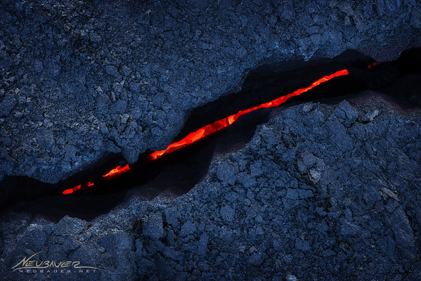 A few years ago I had plans to travel to the Big Island of Hawaii with a photographer friend of mine to shoot the lava fields. They had just had an active run from Kilauea and much of the lava was above the surface and could be seen clearly even during the day. We booked our flights and packed our gear.<br /> <br /> Then a couple days before our trip over a hurricane formed in the eastern Pacific and was bearing down on Hilo, Hawaii, right where we were about to fly into. The next day it was noted that behind that hurricane another had begun to form and would likely follow with a one-two punch on the Big Island.<br /> <br /> Not usually someone to shy away from some action like that, this time it felt like we should postpone our trip. So we did. We waited a couple weeks until the storms were gone and we had the time to get back over there. <br /> <br /> When we got there the lava had stopped its above ground flow and was no longer visible except for where it reached the ocean several miles from any sort of access point. My buddy John and I had hiked for miles trying to find any sign of the glowing red lava with no luck at all.<br /> <br /> Our legs ached as it became dark and we were so far off any marked path we both looked at each other and knew it was time to head back. Defeated. I took my bag off and laid it down on a lava rock in the vast field that surrounded us and took a sip of water from my Nalgene. It was then that I noticed my feet were not just sore and aching, but they were HOT!<br /> <br /> I looked down and found this crack in the rock. Lava flowing directly below us. Before making like Wiley E. Coyote and booking it out of there I snapped a few pictures. This was the best I got. Although not what we were hoping to shoot, I really do like this little crack and the impressive glow of red magma below my feet. <br /> <br /> By the way, I did melt the soles off my shoes from this hike. It was worth it though...
