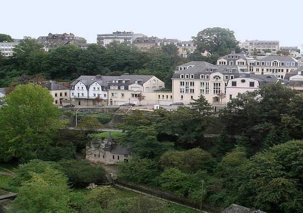 """Across the Pétrusse Valley - to the Quirinus Chapel, constructed into the stone valley wall - with the quarters of Gare (meaning """"station"""") beyond, this quarters of Luxembourg City, was named after the railway station located there."""