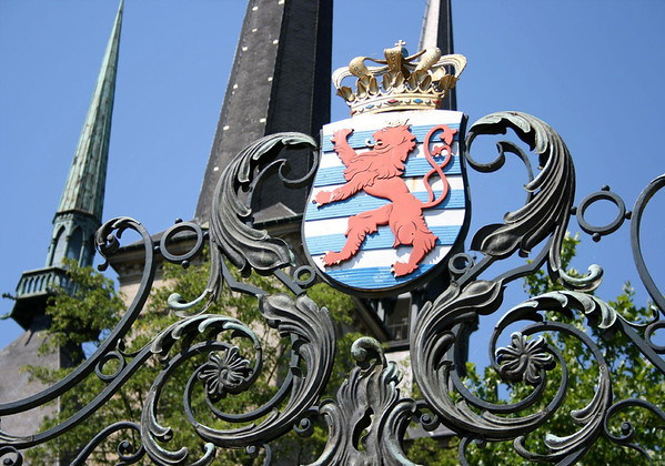 Lesser Coat of Arms, upon the rear gate with the spires atop the Grand Ducal Palace beyond - the official residence of the Grand Duke of Luxembourg - Luxembourg City