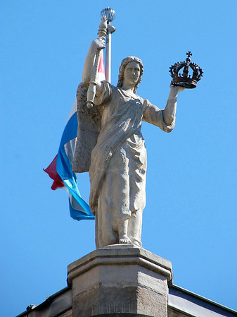 The Luxembourg country flag and statue atop the rear corner of the Chamber of Duties - Luxembourg City