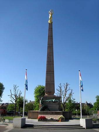 """""""Gëlle Fra"""" (Golden Lady) War Memorial - at Constitution Square - erected in 1923 to commemorate the Luxembourgers who perished in the WW l  - the memorial represents a gilded female figure on a 67 ft. (21 m) tall granite obelisk, holding out a laurel wreath as if placing it upon the head of the nation, at the foot of the obelisk are two bronze figures, representing those Luxembourgish soldiers that volunteered to serve for France; one lies at the base of the statue, having died in service of his country, whilst the other sits, mourning his dead compatriot - Luxembourg City - in 1940 the Nazis pulled the monument down, only in 1984 did extensive restoration give it back its original appearance - today it symbolizes freedom and resistance for the Luxembourg people - Luxembourg City."""