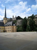 Across the courtyard of the Neumünster Abbey - to the Church of St. John the Baptist - with the St. Michael Church above, along the Chemin de la Corniche - and the Bock Promontory, along the right horizon - Luxembourg City