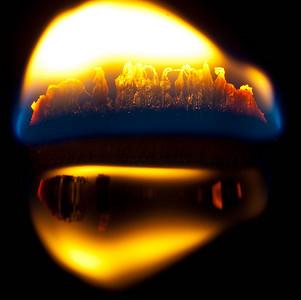 Wood Wick Candle burning, reflection off of dark purple wax. ©JLCramerPhotography 2009