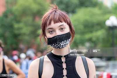 NEW YORK, NEW YORK - JULY 28: A woman wearing a mask with fringe poses in Washington Square Park as the city continues Phase 4 of re-opening following restrictions imposed to slow the spread of coronavirus on July 28, 2020 in New York City. The fourth phase allows outdoor arts and entertainment, sporting events without fans and media production. (Photo by Alexi Rosenfeld/Getty Images)