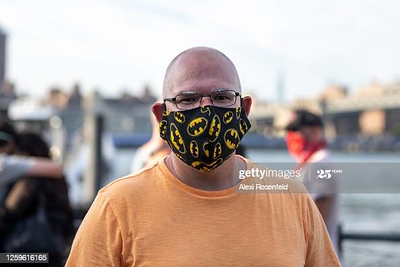 NEW YORK, NEW YORK- JULY 26: A man wearing a 'Batman' mask poses in Dumbo, Brooklyn as the city continues Phase 4 of re-opening following restrictions imposed to slow the spread of coronavirus on July 26, 2020 in New York City. The fourth phase allows outdoor arts and entertainment, sporting events without fans and media production. (Photo by Alexi Rosenfeld/Getty Images)