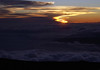 Sunset from atop Haleakala crater - down across the cloud tops to the Ma'alea Bay and the Papawai Point - the western end of West Maui Mountain Volcano