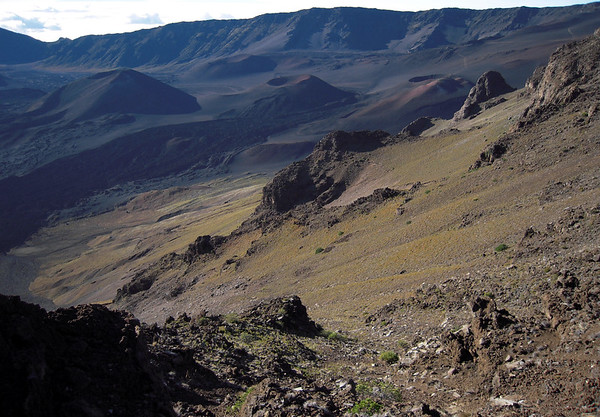 Early morning light upon the eastern slope of the Kilohana Peak - across the Haleakala Crater filled with cinder cones: the Pu'uomaui, Kama'oli'i, and Kalu'ukoa'o'o - with the Pu'uopele cinder cone beyond and the south rim of the crater along the horizon - Haleakala National Park - Upcountry region