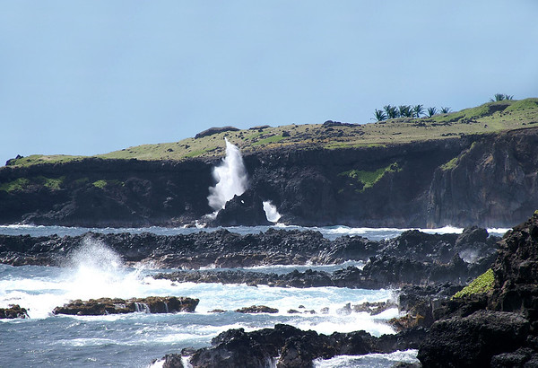 Waves breaking on the volcanic shore at Huakini Bay - with a wave-spray reaching about 40 ft. (12 m) upward, from beyond the igneous rock with the water eroded arch or eye - Southeast island region
