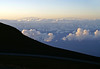 Days's first sunlight from Mauna Haleakala  (House of the Sun Mountain) Volcano - across the cumulus clouds to - Mauna Kea (Snow Mountain) Volcano and Mauna Loa (Long Mountain) Volcano, on the Big Island Hawaii
