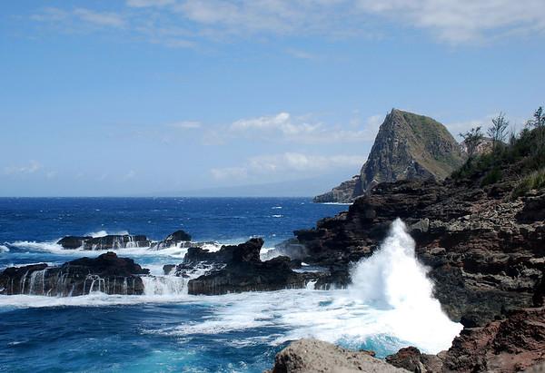Waves crashing on the volcanic rock at Mokolea Point - with Kahakuloa Head beyond the spray - and the northern flank of Mauna Haleakala Volcano along the distal horizon