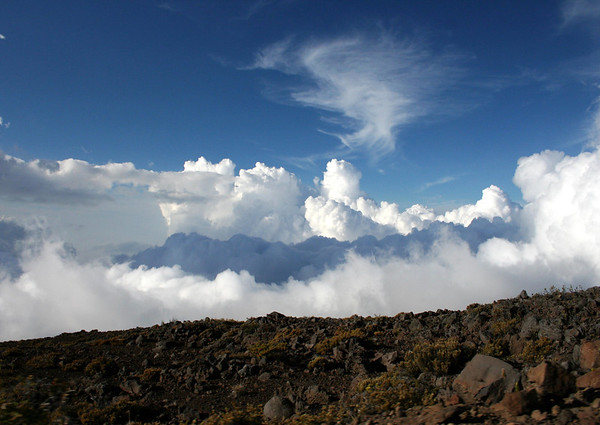 """Across the rim of the Haleakala Crater - towards a """"cloud shadow"""" upon the top of a cumulus cloud - with the cirrus clouds above - Upcountry region"""