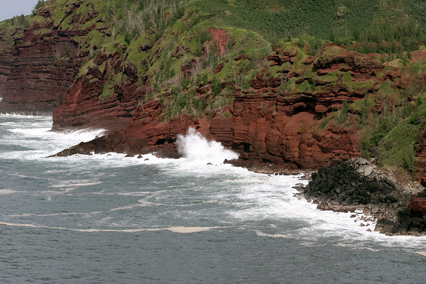 Beyond the red hue sea foam - to the waves crashing upon the iron rich volcanic rock and vegetated cliffs at Honokohau Bay - West Maui region
