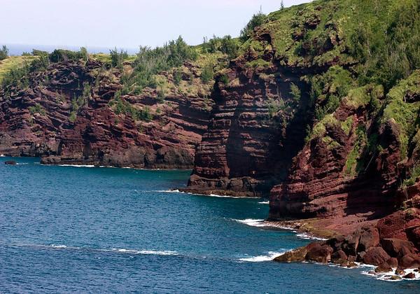 The iron rich extrusive igneous rock and vegetated cliffs, along the the coastline of Honokohau Bay - near Kanounou Point - West Maui region