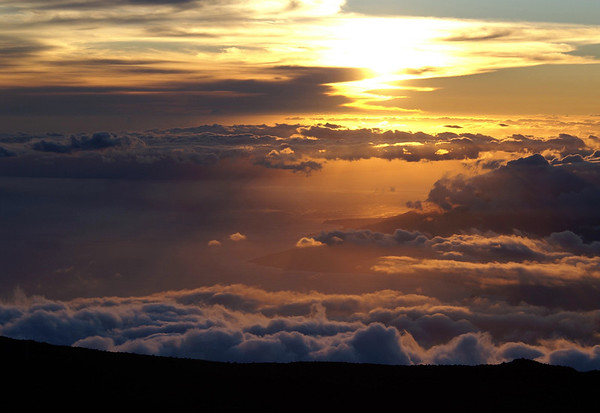 Sunset from atop Mauna Haleakala Volcano - Pu'u'ula'ula Summit  - down over and beyond the clouds to the Ma'alaea Bay at Papawai Point - the western mouth  of the bay and also the southern end of Mauna Kahalawai (West Maui Mountain) Volcano