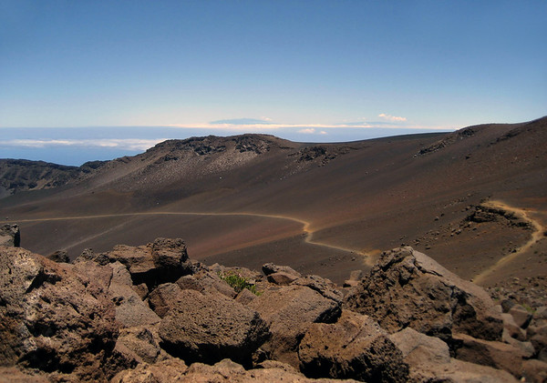 Beyond the extrusive igneous rock to the Sliding Sands (Keonehe'ehe'e) Trail - and the eastern rim of the Haleakala Crater - Upcountry region - with the summits of Mauna Kea and Mauna Loa (Big Island Hawaii), along the distal horizon, above the clouds