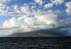 Across Ma'alaea Bay from Kalama Beach Park - South Maui region - to the windmill farm on the Kealaloloa Ridge, situated on the south flank and southern end of the Mauna Kahalawai (West Maui Mountain) Volcano, among the cumulus clouds