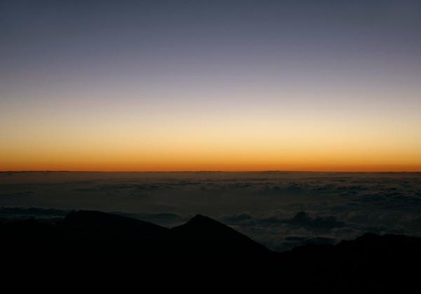 Dawn above the cloud blanket, atop Mauna Haleakala Volcano - Pu'u'ula'ula Summit (Red Hill), rising to 10,023 ft. (3,055 m) - viewing across Haleakala peak 8,201 ft. (2,500 m) the western beginning of the Kaupo Gap - Haleakala National Park - Upcountry region