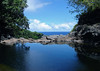 Infinity Pool - atop the Waimoku Falls - looking out across the volcanic rock ledge, into the Pacific Ocean and the cumulus clouds above - Haleakala National Park - Southeast island region