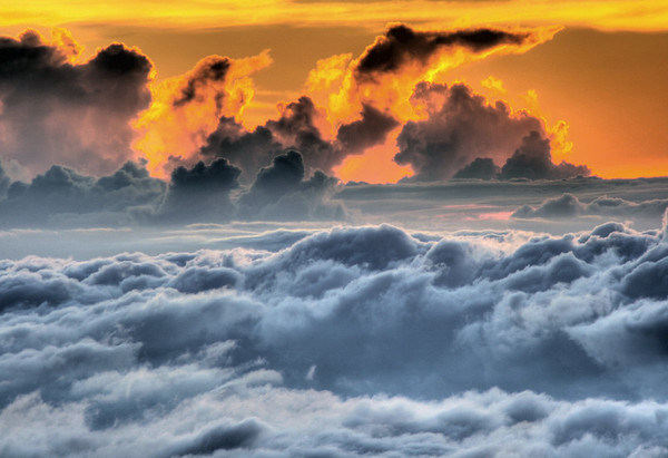 Sunset glow beyond the distal edge of the tops of the cumulus clouds - from atop the summit of the Haleakala crater - Upcountry region