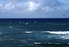 Wind surfers and a solo kite boarder (kite surfer) - at Ho'okipa Beach - North Shore region