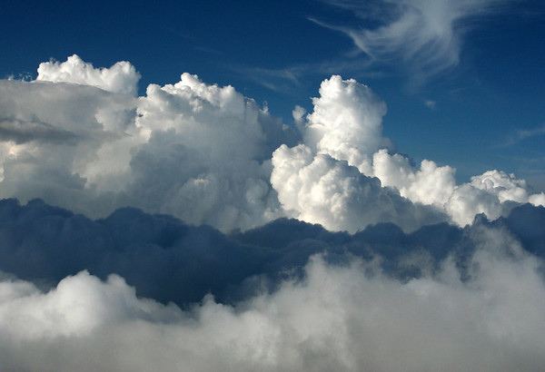 Down towards a cloud shadow, upon the top of a cumulus cloud - with a cirrus cloud above - Upcountry region