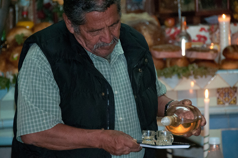 "Augustín's father pours mescal for visitors. The Zopotec communites are closed and normally a ""gringo"" like me wouldn't be allowed to visit, especially during Night of the Dead."