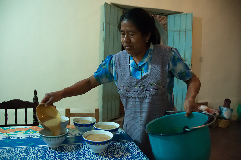 A host pours bowls of atole, a corn-based drink that is alcohol free.