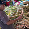 Cutting sugar cane at a market.