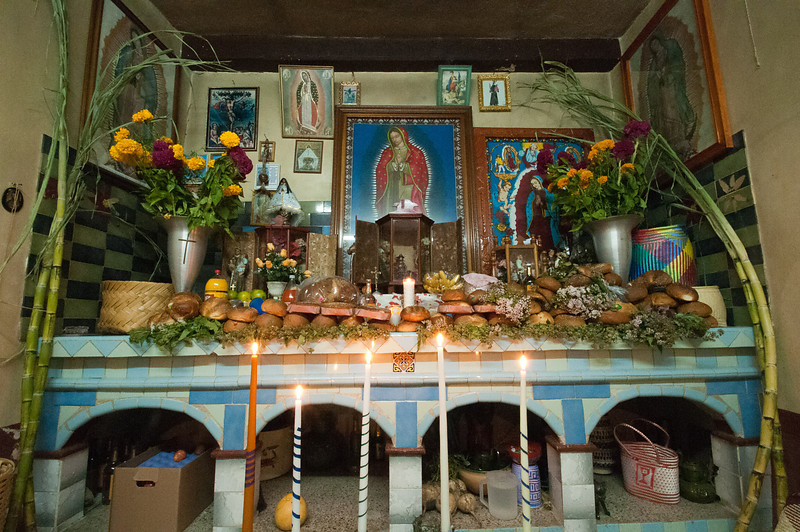 Every house includes a room with a permanent altar-type structure. During Day of the Dead the altar is decorated with photos of the deceased, paintings of saints, etc. It is also festooned with loaves of bread (pan), maybe opened beer, other food and drinks and lit candles. The placement of everything on the altar is set by tradition.