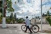 A man walks his bicycle through the town square. (Pisté, Yucatán, MX - 01/14/16, 2:33:33 PM)