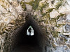 Man walking through a narrow and low stone tunnel at the Coba ruins, Yucatan Peninsula, Mexico