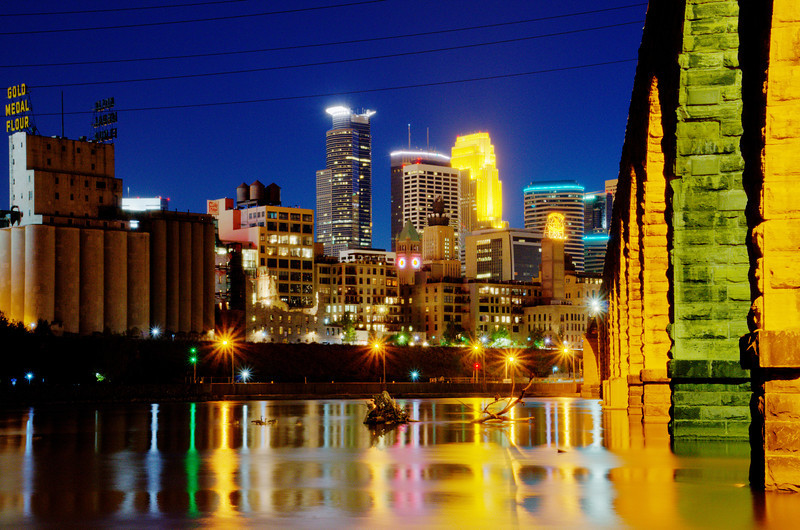Downtown Minneapolis reflecting in the Mississippi River. The Stone Arch Bridge is on the left.
