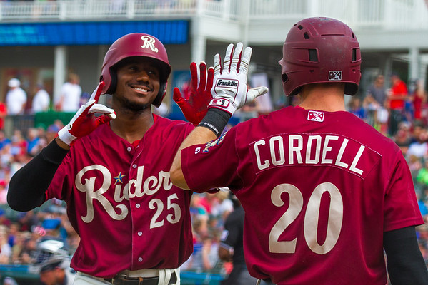 Frisco RoughRiders' Lewis Brinson (25) high-fives teammate Ryan Cordell (20) after Brinson hit a solo home run in the first inning of a game against the San Antonio Missions at Dr. Pepper Ballpark in Frisco, Texas, Sunday, May 22, 2016. (Photo by Sam Hodde)