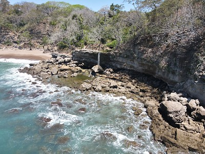 Lush Tropical Beach Paradise with blue water, great waves and rock formations in Montezuma Nicoya Peninsula Costa Rica