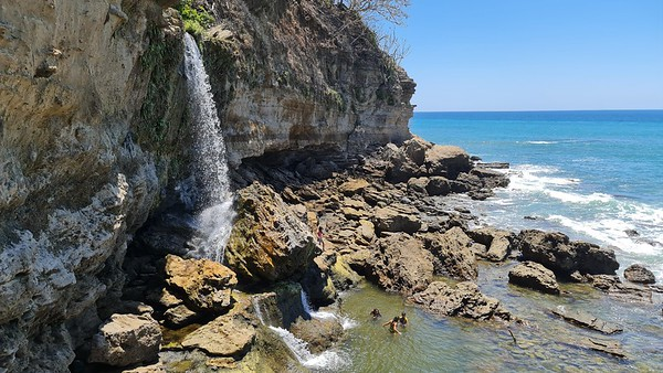 Waterfall into the ocean in a rock formations in Montezuma Nicoya Peninsula Costa Rica