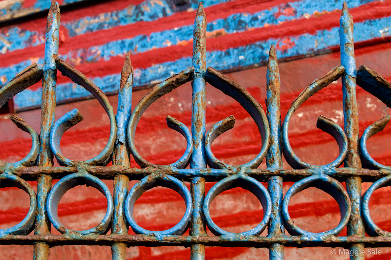 Old iron fence with colourful boat in dry dock behind.