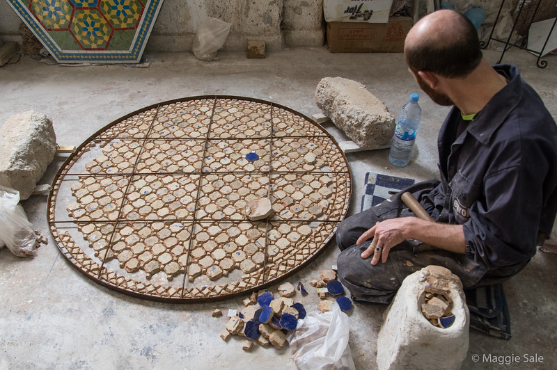 Mosaic table tops being created at a Fez pottery. The pieces are added upside down  and colour patterns have to be memorized.
