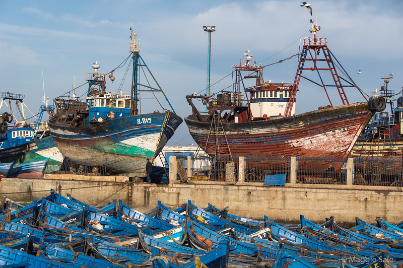 Ship repairs and blue fishing boats in Essaouira.