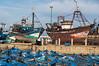 Ship repairs and blue fishing boats in Essaouira.